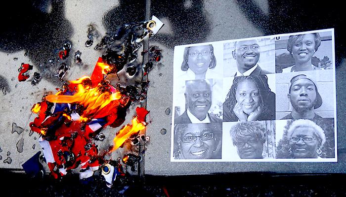 Retrato de las víctimas de la masacre de Charleston junto a una bandera de los Estados Confederados en llamas.
