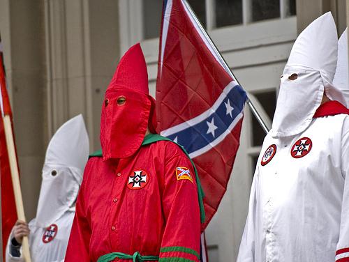 Miembros del Ku Klux Klan con la bandera de los Estados Confederados al fondo.