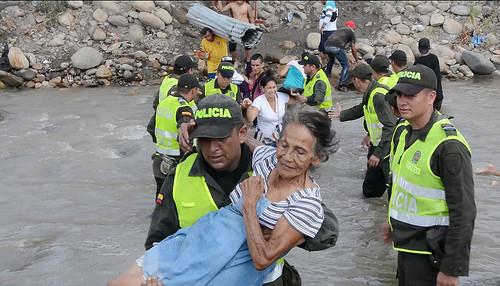 Oficiales de la Policía Nacional ayudan a refugiados colombianos en su éxodo hacia la ciudad de Cúcuta.